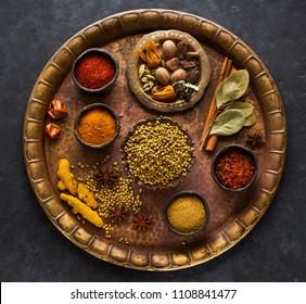 Indian spices, spicy and seasoning in bowls on a brass tray, top view