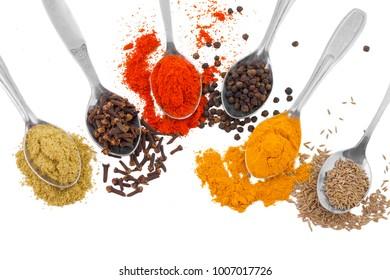 Indian Spices in Spoons Also Know as Red Chilli Powder, Black Pepper, Turmeric Powder, Coriander Powder, Cumin, Cloves, Mirchi, Mirch, Laal Mirchi, Haldi, Dhaniya Powder, Jeera, Kali Mirch or Lavang.
