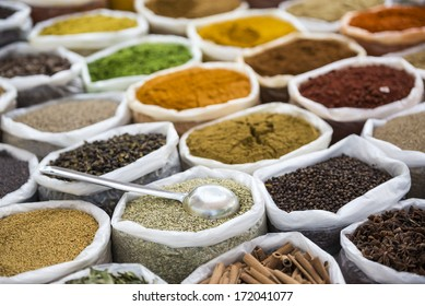 Indian spices in white sacks with scoop.