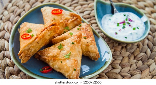 Indian Spicy Vegetable samosa with Mint Yoghurt Raita. A samosa , sambusa, sambuus, samoosa, or samboksa is a fried or baked dish with a savoury filling, such as spiced potatoes, onions, peas, lentils