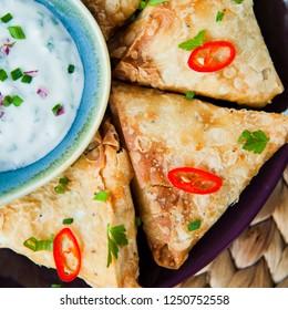 Indian Spicy Vegetable samosa with Mint Yoghurt Raita. A samosa , sambusa, sambuus, samoosa, or samboksa is a fried or baked dish with a savoury filling, such as spiced potatoes, onions, peas, lentils