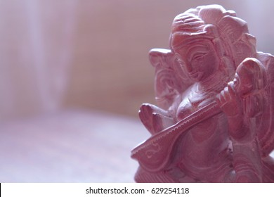 Indian stone statuette - Goddess Saraswati plays on wine. Delicate pink background on the musical theme, as the concept of oriental music, the evening of Indian culture, the creativity of Asia.
