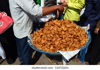 Indian street food vendor sell samosas a popular variety in a busy road