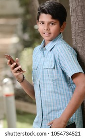 Indian student kid with a cell phone in hand