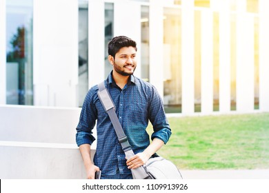 Indian student with smartphone and bag standing outdoor