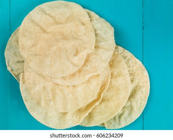 Indian Style Crispy Thin Poppadoms Against a Blue Background