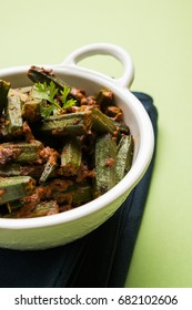Indian style Masala Sabji OR Sabzi of fried Bhindi OR Okra also known as Ladyfinger, Served in a bowl over moody background. selective focus