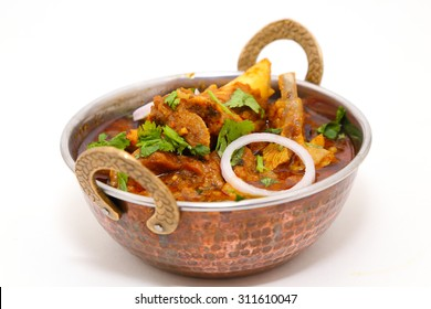 Indian style meat dish or mutton curry in a copper brass bowl isolated on white background.