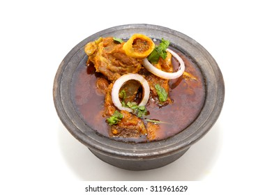 Indian style meat dish or mutton curry in a black clay pot bowl isolated on white background.