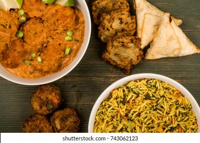 Indian Style Vegetable Kofta Curry Meal On A Green Wooden Background With Pillau Rice and Samosas Onion Bhaji and Pakoras