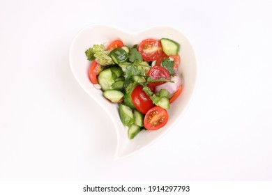 Indian Subcontinent style tomato cucumber onion chili coriander salad in hart shape white dish on white background
