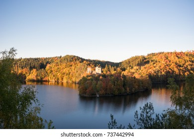 Indian summer on a lake with an old ruine and colorful trees reflecting in the water