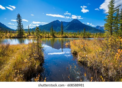 Indian summer in the Rocky Mountains of Canada. Shallow Lake Vermilion is surrounded by mountains and forests