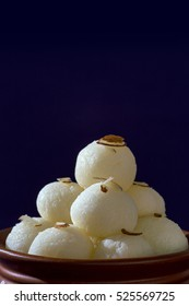 Indian Sweet or Dessert - Rasgulla, Famous Bengali sweet in clay bowl on violet background