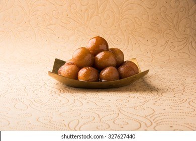 indian sweet gulab jamun in square shape brass plate, closeup view on cream paper with floral design, isolated