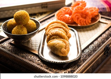 Indian sweet Jalebi/Imarti, Laddu and Gujiya served together over white background or with gifts. Selective focus