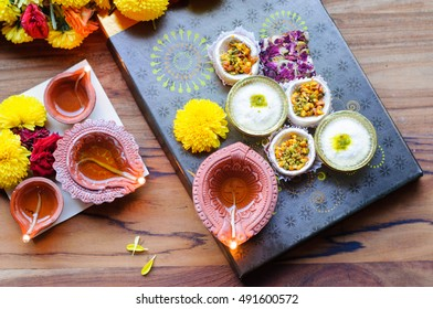 Indian sweet or mithai and oil lamps or diyas with flowers on a wooden table
