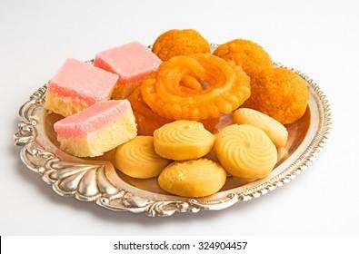 indian sweet pedha, jalebi, motichoor / bundi laddu and  burfi in a silver plate isolated on white background