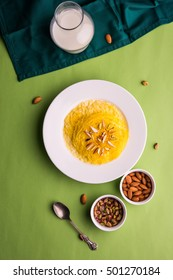Indian sweet Saffron Flavoured Sutarfeni or Firni / Seviyan / Laccha topped with pistachio & almonds to be eaten with warm milk. Served in a bowl over colourful or wooden background. Selective focus
