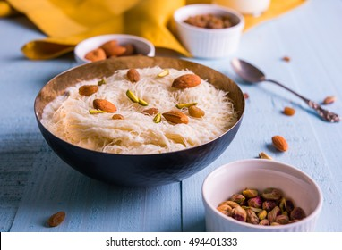Indian sweet Sutarfeni or Firni or Seviyan or Laccha topped with pistachio and almonds to be eaten with warm milk. Served in a bowl over colourful or wooden background. Selective focus