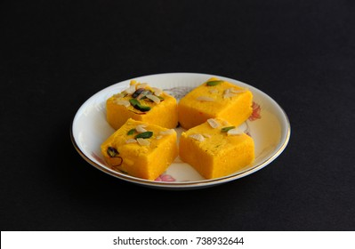 Indian sweets kaju barfi or kalakand in white plate on the table with black background
