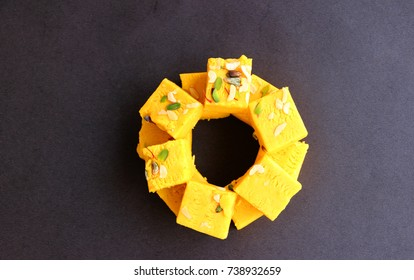 Indian sweets kaju barfi or kalakand isolated on the table with black background