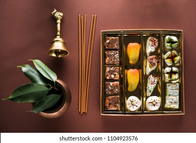 Indian sweets and Mithai in a box, insense sticks and bell. Diwali festival concept, flat lay, top view