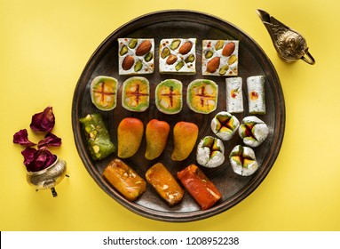 Indian sweets and Mithai on a copper tray for Diwali festival, flat lay, top view
