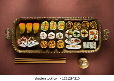 Indian sweets and Mithai in a tray, incense and bell for Diwali festival, flat lay, top view