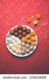 Indian sweets in a plate includes Gulab Jamun, Rasgulla, kaju katli, morichoor / Bundi Laddu, Gujiya or Karanji for diwali celebration