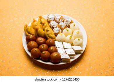 Indian sweets in a plate includes Gulab Jamun, Rasgulla, kaju katli, morichoor / Bundi Laddu, Gujiya or Karanji for diwali celebration