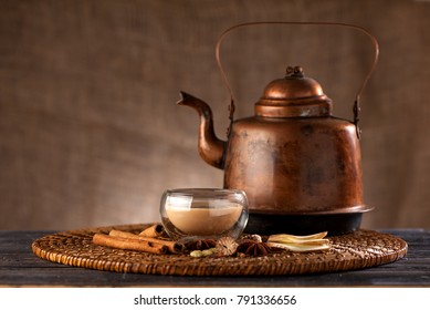 Indian tea with milk and spices masala chai in a copper kettle and cup