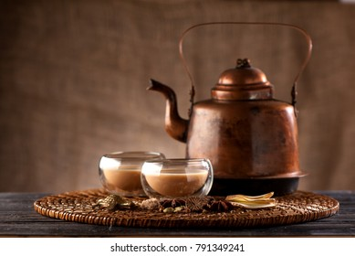 Indian tea with milk and spices masala chai in a copper kettle and cups