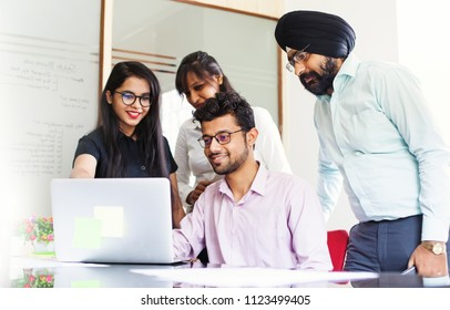 Indian team working together and looking on a screen of laptop