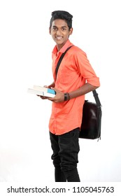 Indian teen boy along with his books and laptop on white background