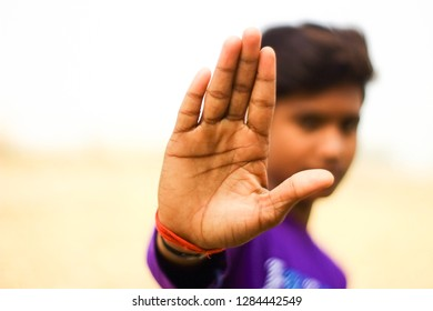 An Indian teen model showing his hand as a sign for stop something with colorful blurry background. Copy space.