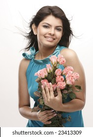 Indian teenage girl with happy expression carrying bunch of pink roses