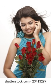 Indian teenage girl talking over cellphone with bunch of red roses
