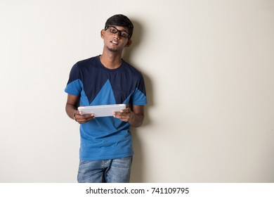 indian teenage male on tablet computer