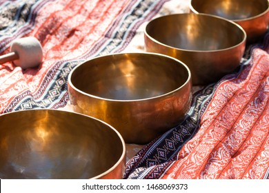 Indian Tibetan bronze healing bowls lie on a sari in perspective. Singing healing bowls of Tibetan traditional medicine. Sounding sacred music for healing.