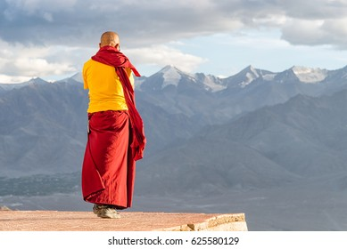 Indian tibetan monk lama in red and yellow color clothing standing in front of mountains