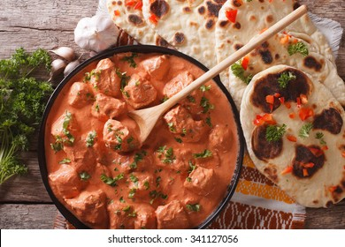 Indian tikka masala chicken and naan flat bread close-up on the table. horizontal top view