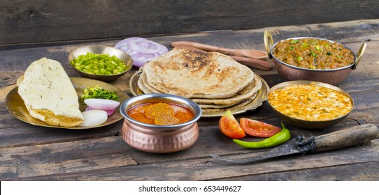 Indian Traditional Cuisine Gatta Curry Also Called Gatte ki Sabji or Besan Gatta is a Rajasthan Famous Food Served with Chapati, Onion, Raita or Papad on Wooden Background