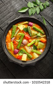 Indian traditional curry recipe- sambhar served in bowl ,on a wooden table.