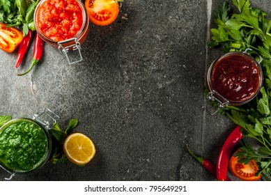Indian traditional food, Set of three chutney for Chaat and Sev Puri - sweet date-tamarind, cilantro-mint green and red chilli garlic, On dark stone background, copy space top view frame