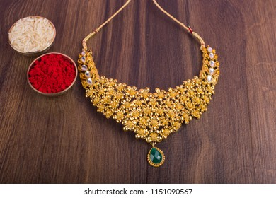 Indian Traditional Gold Jewellery Necklace with kumkum and grain rice.