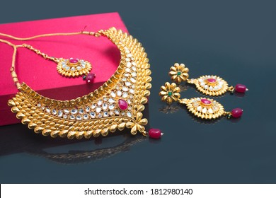 Indian Traditional Jewellery with earring, mangteeka and beautiful  box on black background. selective focus