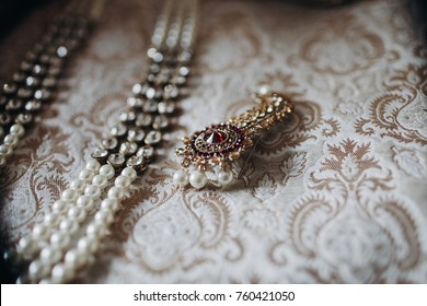Indian traditional jewerly made od pearls and re precious stones lies on the rich embroidered cloth