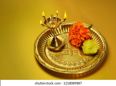 Indian traditional oil lamp and marigold flower in a brass plate. Religious objects.