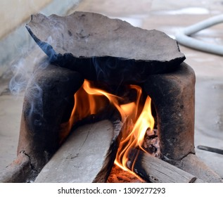 Indian traditional stove or oven. Wood burning under the clay pan. Ready to prepare Indian bread or chapatti. Flames.